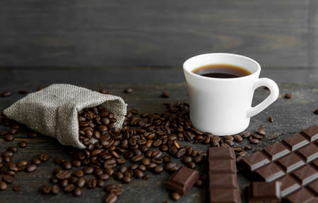 Coffee beans scattered from a linen bag on a wooden table. Cup of coffee and bar of dark chocolate. Mug of black coffee. Morning coffee with a chocolate.