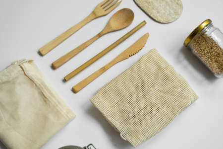 Zero waste kit. Set of eco friendly bamboo cutlery, mesh cotton bags, glass jars and loofah sponge. Plastic free. Natural and reusable items accessories on gray surface.