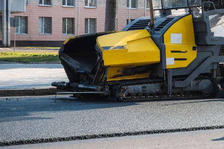Industrial asphalt paver machine laying fresh asphalt on road construction site on the street.