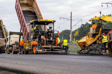 KYIV, UKRAINE - September 25, 2020: Industrial asphalt paver machine laying fresh asphalt on road construction site.
