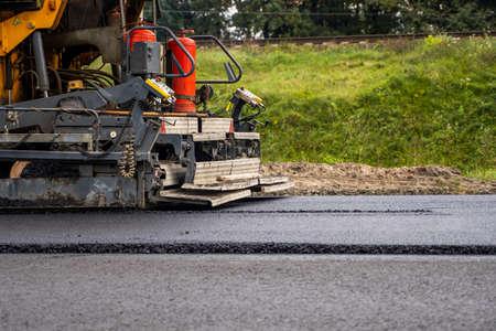 Industrial asphalt paver machine laying fresh asphalt on road construction site. 写真素材