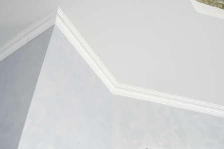 White ceiling with a white plinth in a room with gray painted walls. Decoration of the corner between the ceiling and the wall in the room. Ceiling molding in the interior. Detail of corner.