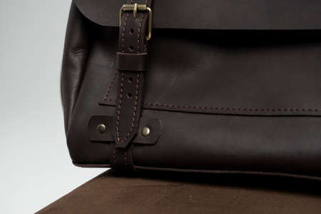 Details of brown mens shoulder leather bag for a documents and laptop on a brown chair with a white background. Mens leather brief case, messenger bags, leather satchel, handmade briefcase.