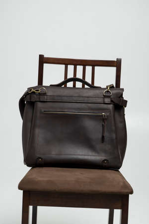 Brown mens shoulder leather bag for a documents and laptop on a brown chair with a white background. Mens leather brief case, messenger bags, leather satchel, handmade briefcase. 写真素材 - 162437752