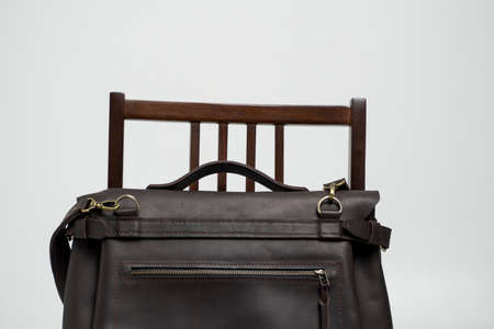 Brown mens shoulder leather bag for a documents and laptop on a brown chair with a white background. Mens leather brief case, messenger bags, leather satchel, handmade briefcase. 写真素材 - 162437753
