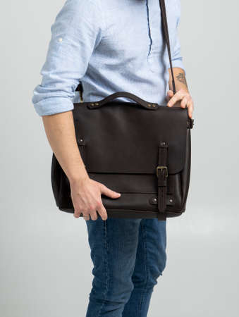 Brown mens shoulder leather bag for a documents and laptop on the shoulders of a man in a blue shirt and jeans with a white background. Satchel, mens leather handmade briefcase. 写真素材 - 162437755