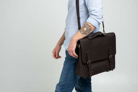Brown mens shoulder leather bag for a documents and laptop on the shoulders of a man in a blue shirt and jeans with a white background. Satchel, mens leather handmade briefcase. 写真素材 - 162437789