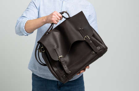 Brown mens shoulder leather bag for a documents and laptop on the shoulders of a man in a blue shirt and jeans with a white background. Satchel, mens leather handmade briefcase. 写真素材