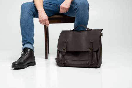 Man in a blue jeans and black boots sits on a chair with a brown mens shoulder leather bag for a documents and laptop on a white floor. Mens leather satchel, messenger bags, handmade briefcase.
