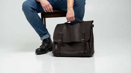 Man in a blue jeans and black boots sits on a chair with a brown mens shoulder leather bag for a documents and laptop on a white floor. Mens leather satchel, messenger bags, handmade briefcase. 写真素材