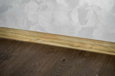 Laminate with plastic baseboard with a wooden texture. Newly installed wooden laminate flooring and baseboards in home. Modern design. Close up of plastic plinths on dark wooden oak floor parquet. 写真素材 - 162437802