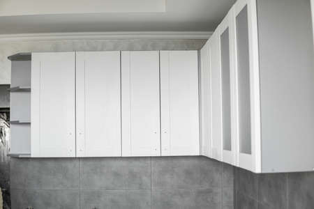 Custom kitchen cabinets installation with a white furniture facades mdf. Gray modular kitchen from chipboard material on a various stages of installation. A frame furniture fronts mdf profile. 写真素材 - 162437815