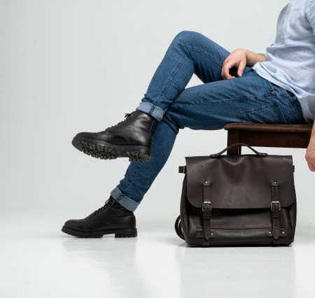 Man in a blue jeans and black boots sits on a chair with a brown mens shoulder leather bag for a documents and laptop on a white floor. Mens leather satchel, messenger bags, handmade briefcase. 写真素材 - 162437822