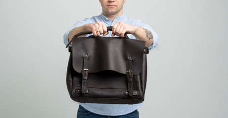 Brown mens shoulder leather bag for a documents and laptop holds by man in a blue shirt and jeans with a white background. Satchel, mens leather handmade briefcase. 写真素材 - 162437847