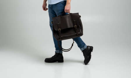 Brown mens shoulder leather bag for a documents and laptop holds by man in a blue shirt and jeans with a white background. Satchel, mens leather handmade briefcase. 写真素材 - 162437849