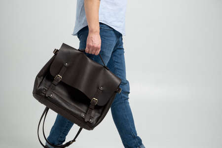 Brown mens shoulder leather bag for a documents and laptop holds by man in a blue shirt and jeans with a white background. Satchel, mens leather handmade briefcase. 写真素材 - 162437850