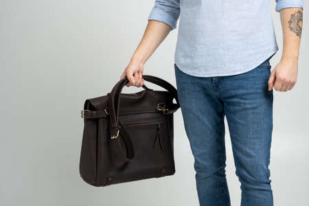 Brown mens shoulder leather bag for a documents and laptop holds by man in a blue shirt and jeans with a white background. Satchel, mens leather handmade briefcase. 写真素材 - 162437853