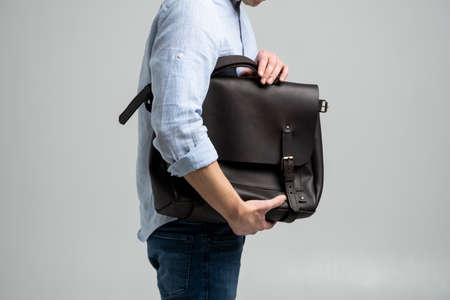 Brown mens shoulder leather bag for a documents and laptop holds by man in a blue shirt and jeans with a white background. Satchel, mens leather handmade briefcase. 写真素材 - 162437854