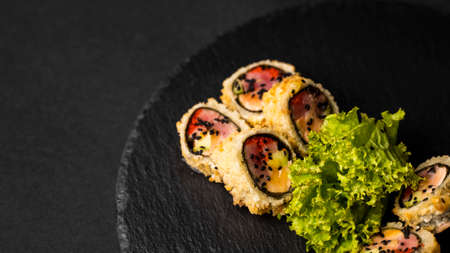 Custom sushi roll in tempura with nori, fresh salmon, tuna, avocado, masago caviar, drizzled with pineapple sauce with salad pouring as decoration on a black plate on a black table and background. 写真素材 - 162437863