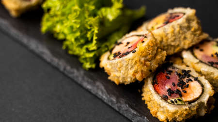 Custom sushi roll in tempura with nori, fresh salmon, tuna, avocado, masago caviar, drizzled with pineapple sauce with salad pouring as decoration on a black plate on a black table and background. 写真素材 - 162437865