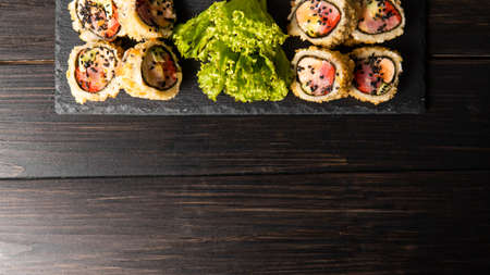 Custom sushi roll in tempura with nori, fresh salmon, tuna, avocado, masago caviar, drizzled with pineapple sauce with salad pouring as decoration on a black plate on a wooden table and background. 写真素材 - 162437867