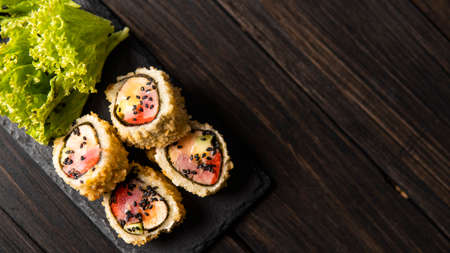 Custom sushi roll in tempura with nori, fresh salmon, tuna, avocado, masago caviar, drizzled with pineapple sauce with salad pouring as decoration on a black plate on a wooden table and background.