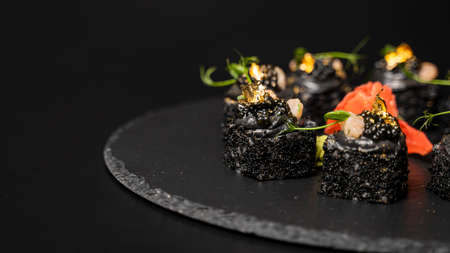 Sushi roll with nori, black rice, crab meat, cucumber, avocado, smoked salmon mousse, oar caviar, masago, shrimp cocktail and edible gold leaf with red ginger and wasabi on black table and background.