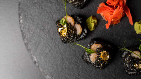 Sushi roll with nori, black rice, crab meat, cucumber, avocado, smoked salmon mousse, oar caviar, masago, shrimp cocktail and edible gold leaf with red ginger and wasabi on black table and background. 写真素材 - 162437884