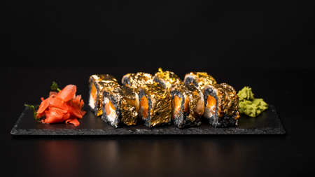 Custom sushi roll with nori, cuttlefish ink, fresh salmon, cream cheese, pepper pumpkin, eel, unagi sauce and edible gold leaf with red ginger, wasabi on a square plate on black table and background. 写真素材 - 162437885