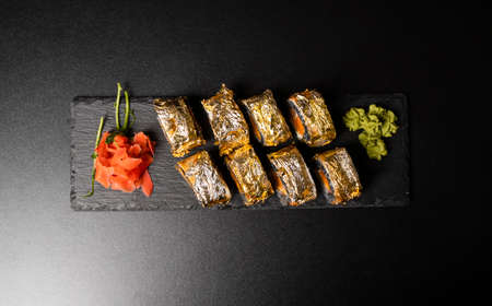 Custom sushi roll with nori, cuttlefish ink, fresh salmon, cream cheese, pepper pumpkin, eel, unagi sauce and edible gold leaf with red ginger, wasabi on a square plate on black table and background. 写真素材 - 162437887