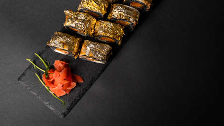 Custom sushi roll with nori, cuttlefish ink, fresh salmon, cream cheese, pepper pumpkin, eel, unagi sauce and edible gold leaf with red ginger, wasabi on a square plate on black table and background. 写真素材 - 162437892