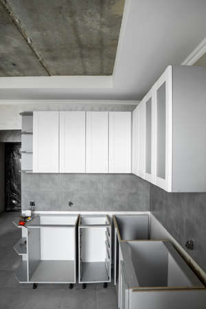 Custom kitchen cabinets installation with a white furniture facades mdf. Gray modular kitchen from chipboard material on a various stages of installation. A frame furniture fronts mdf profile.