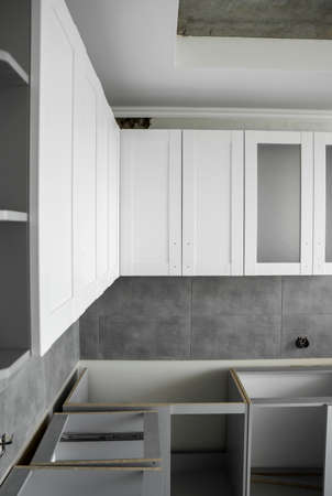 Custom kitchen cabinets installation with a white furniture facades mdf. Gray modular kitchen from chipboard material on a various stages of installation. A frame furniture fronts mdf profile. 写真素材 - 162437903