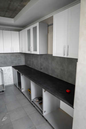 Custom kitchen cabinets installation with a white furniture facades mdf. Gray modular kitchen from chipboard material on a various stages of installation. A frame furniture fronts mdf profile. 写真素材 - 162437907
