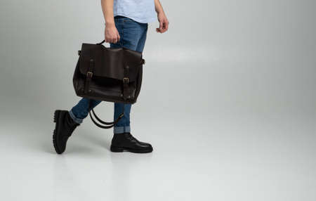 Brown mens shoulder leather bag for a documents and laptop holds by man in a blue shirt and jeans with a white background. Satchel, mens leather handmade briefcase. 写真素材 - 162437928