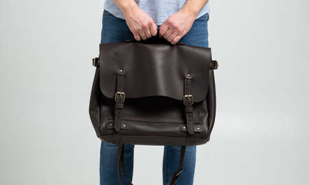 Brown mens shoulder leather bag for a documents and laptop holds by man in a blue shirt and jeans with a white background. Satchel, mens leather handmade briefcase.