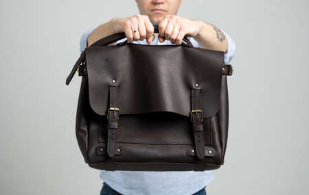 Brown mens shoulder leather bag for a documents and laptop holds by man in a blue shirt and jeans with a white background. Satchel, mens leather handmade briefcase. 写真素材 - 162437931