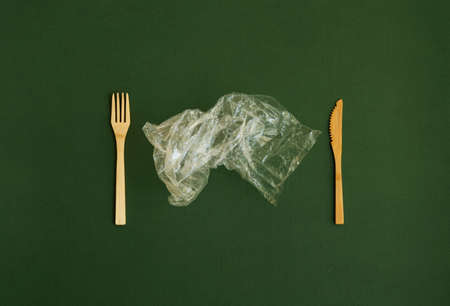 Crumpled plastic polyethylene bag with a bamboo fork and knife on a green background. Contamination of the planet. Clear plastic bag. Zero waste concept. 写真素材