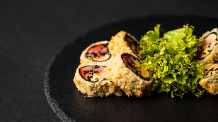Custom sushi roll in tempura with nori, fresh salmon, tuna, avocado, masago caviar, drizzled with pineapple sauce with salad pouring as decoration on a black plate on a black table and background. 写真素材 - 162437939