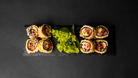 Custom sushi roll in tempura with nori, fresh salmon, tuna, avocado, masago caviar, drizzled with pineapple sauce with salad pouring as decoration on a black plate on a black table and background.