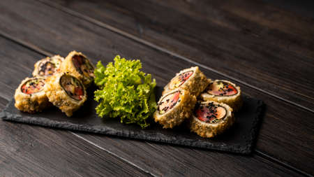 Custom sushi roll in tempura with nori, fresh salmon, tuna, avocado, masago caviar, drizzled with pineapple sauce with salad pouring as decoration on a black plate on a wooden table and background. 写真素材 - 162437942