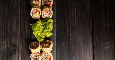 Custom sushi roll in tempura with nori, fresh salmon, tuna, avocado, masago caviar, drizzled with pineapple sauce with salad pouring as decoration on a black plate on a wooden table and background. 写真素材 - 162437947