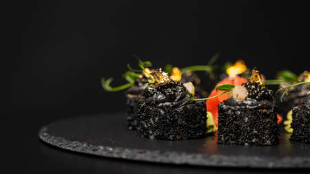 Sushi roll with nori, black rice, crab meat, cucumber, avocado, smoked salmon mousse, oar caviar, masago, shrimp cocktail and edible gold leaf with red ginger and wasabi on black table and background. 写真素材 - 162437950