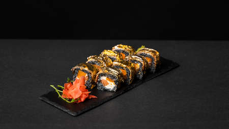 Custom sushi roll with nori, cuttlefish ink, fresh salmon, cream cheese, pepper pumpkin, eel, unagi sauce and edible gold leaf with red ginger, wasabi on a square plate on black table and background. 写真素材 - 162437955