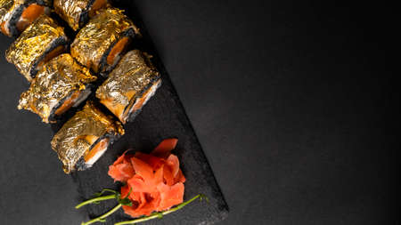 Custom sushi roll with nori, cuttlefish ink, fresh salmon, cream cheese, pepper pumpkin, eel, unagi sauce and edible gold leaf with red ginger, wasabi on a square plate on black table and background. 写真素材 - 162437956