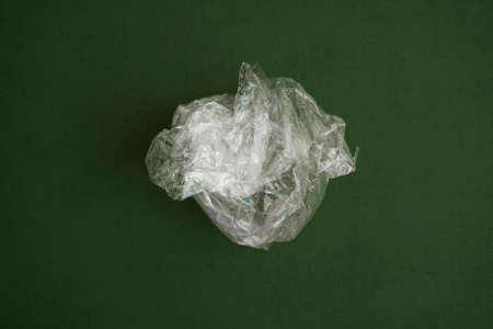 Crumpled plastic polyethylene bag on a green background. Contamination of the planet. Clear plastic bag. Zero waste concept.