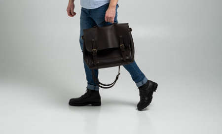 Brown mens shoulder leather bag for a documents and laptop holds by man in a blue shirt and jeans with a white background. Satchel, mens leather handmade briefcase. 写真素材 - 162437958