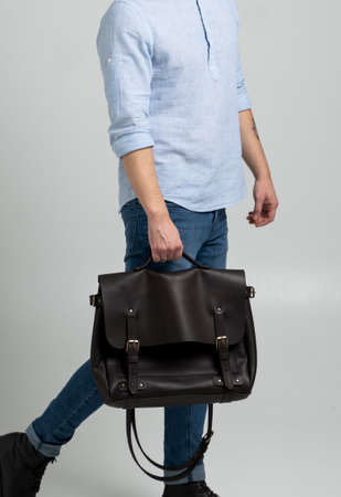 Brown mens shoulder leather bag for a documents and laptop holds by man in a blue shirt and jeans with a white background. Satchel, mens leather handmade briefcase. 写真素材 - 162437964