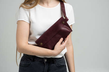 Girl in a white blouse with a leather red handmade bag over her shoulder. Designer dark red banana bag. Woman in a studio. Comfortable small bag for walking. Zdjęcie Seryjne