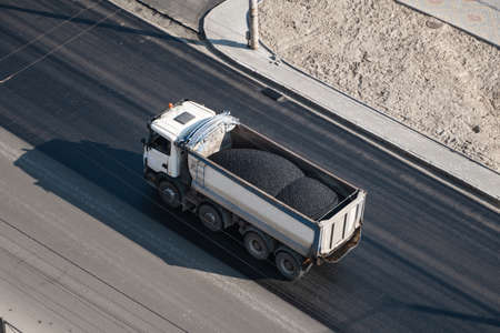 Truck with a breakstone on a road in the city during road construction work. Reklamní fotografie